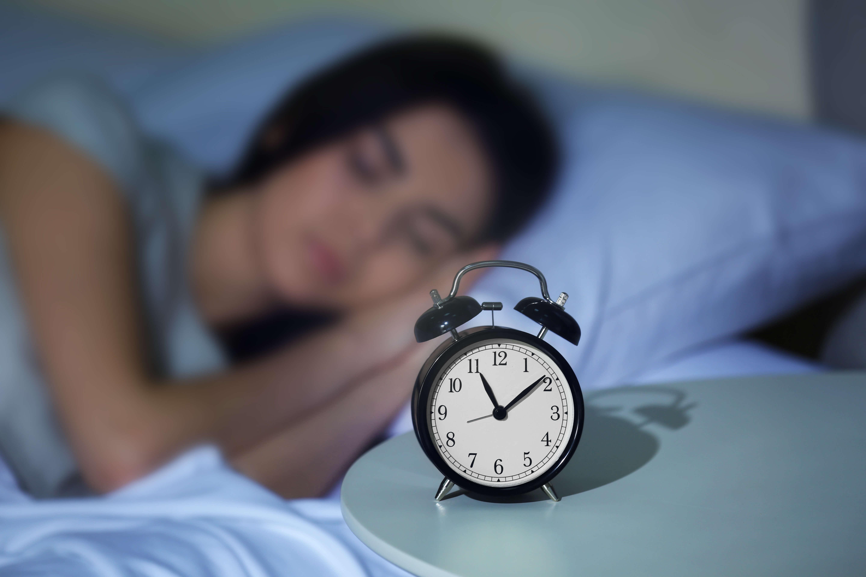 睡眠中の女性と目覚まし時計