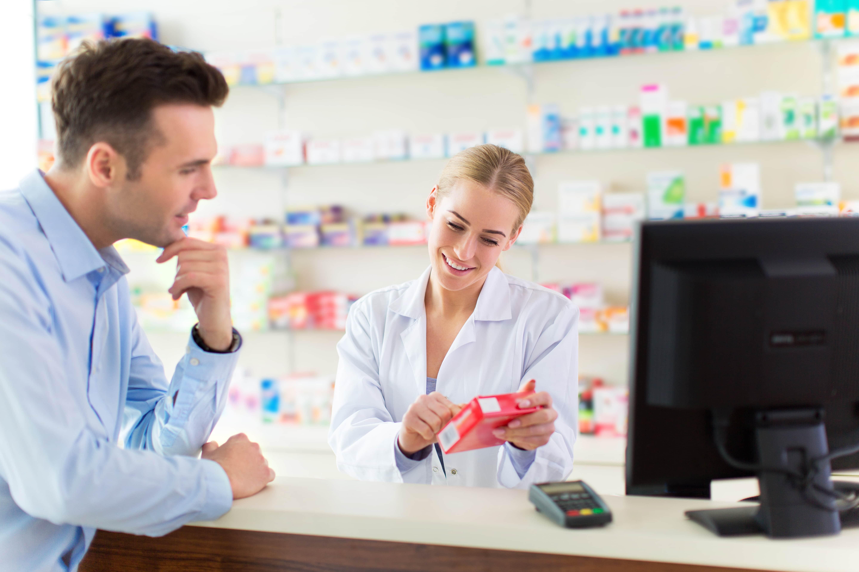 薬局で女性薬剤師に説明を聞く男性