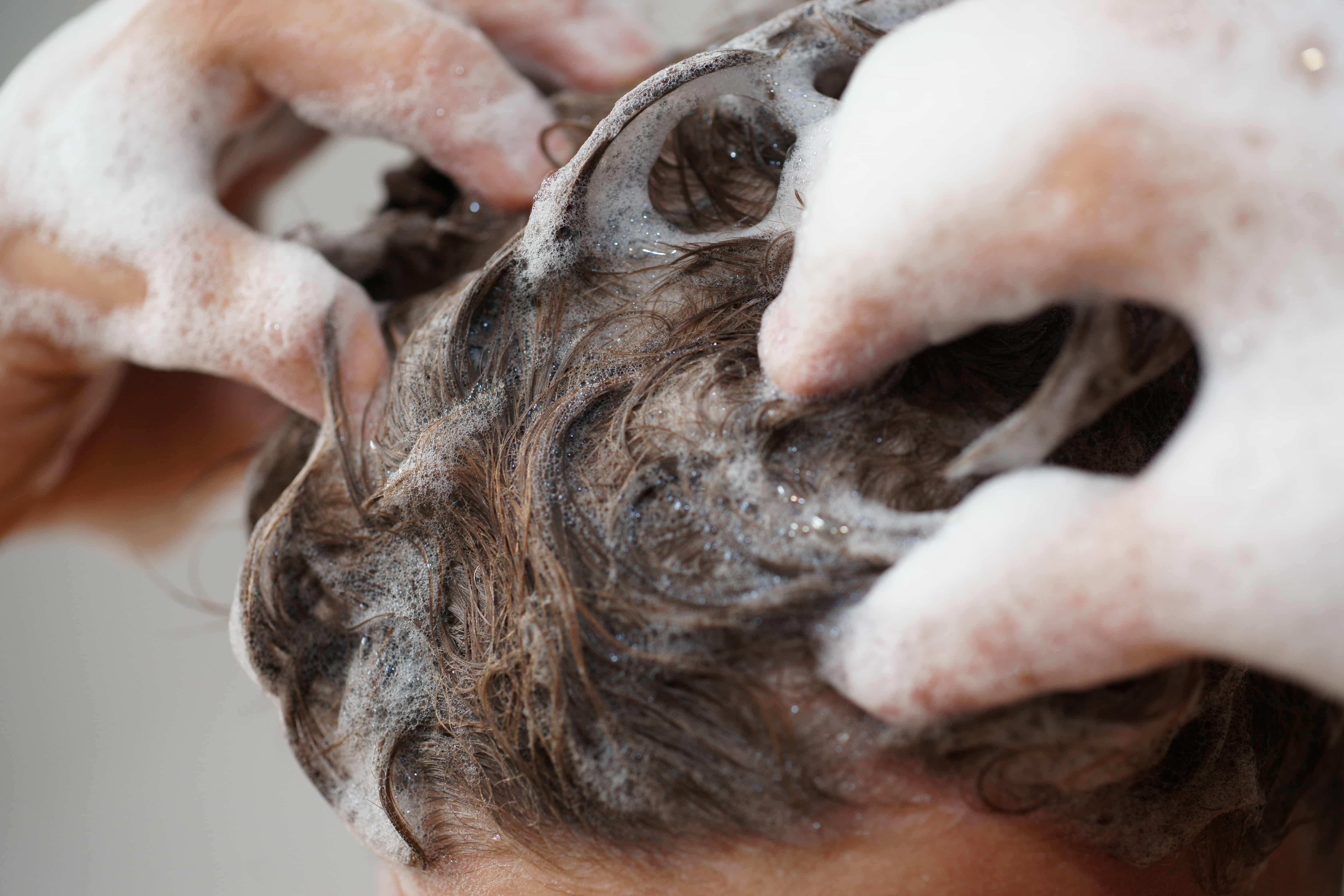 髪をシャンプーする手