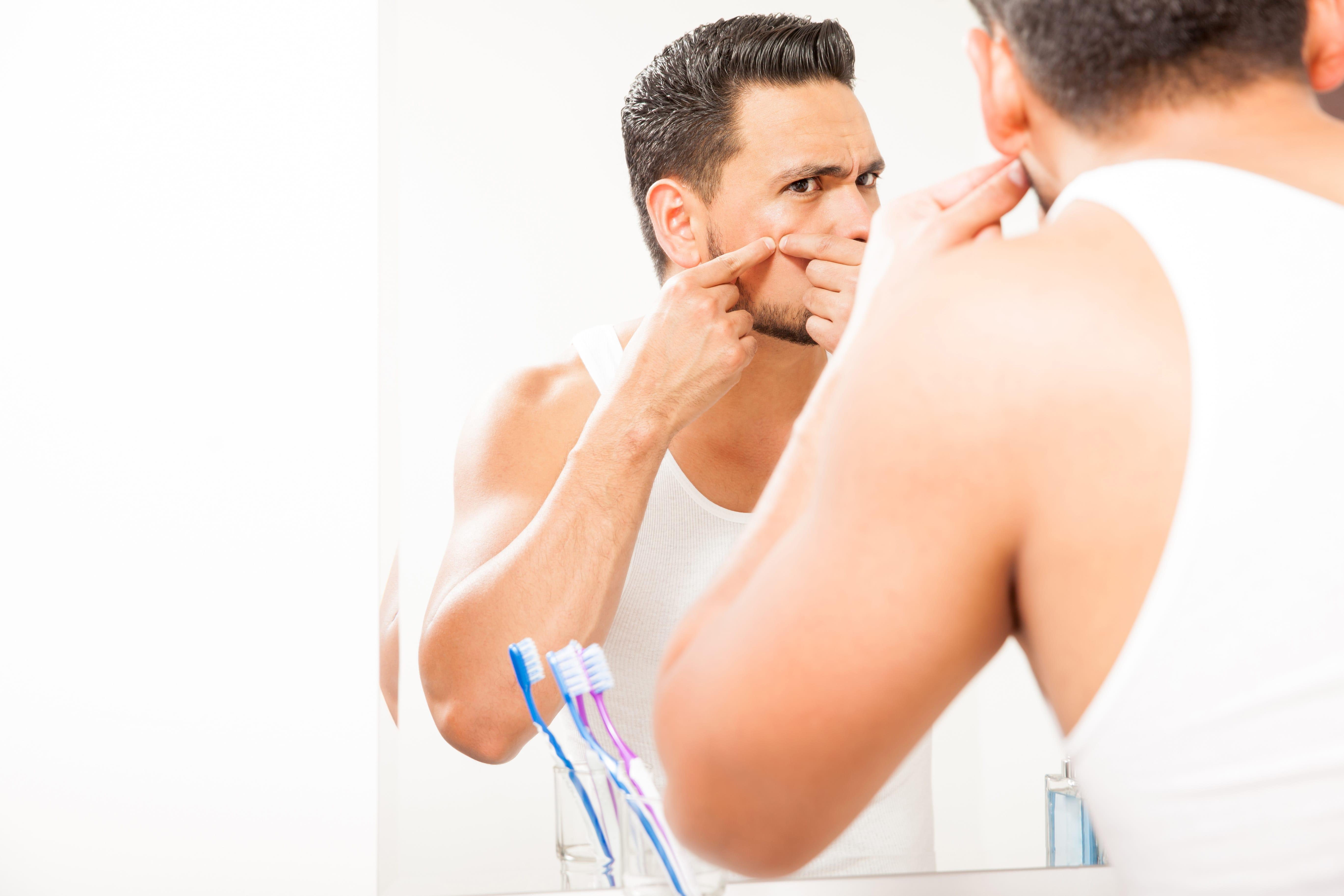 鏡でで顔を見ている男性