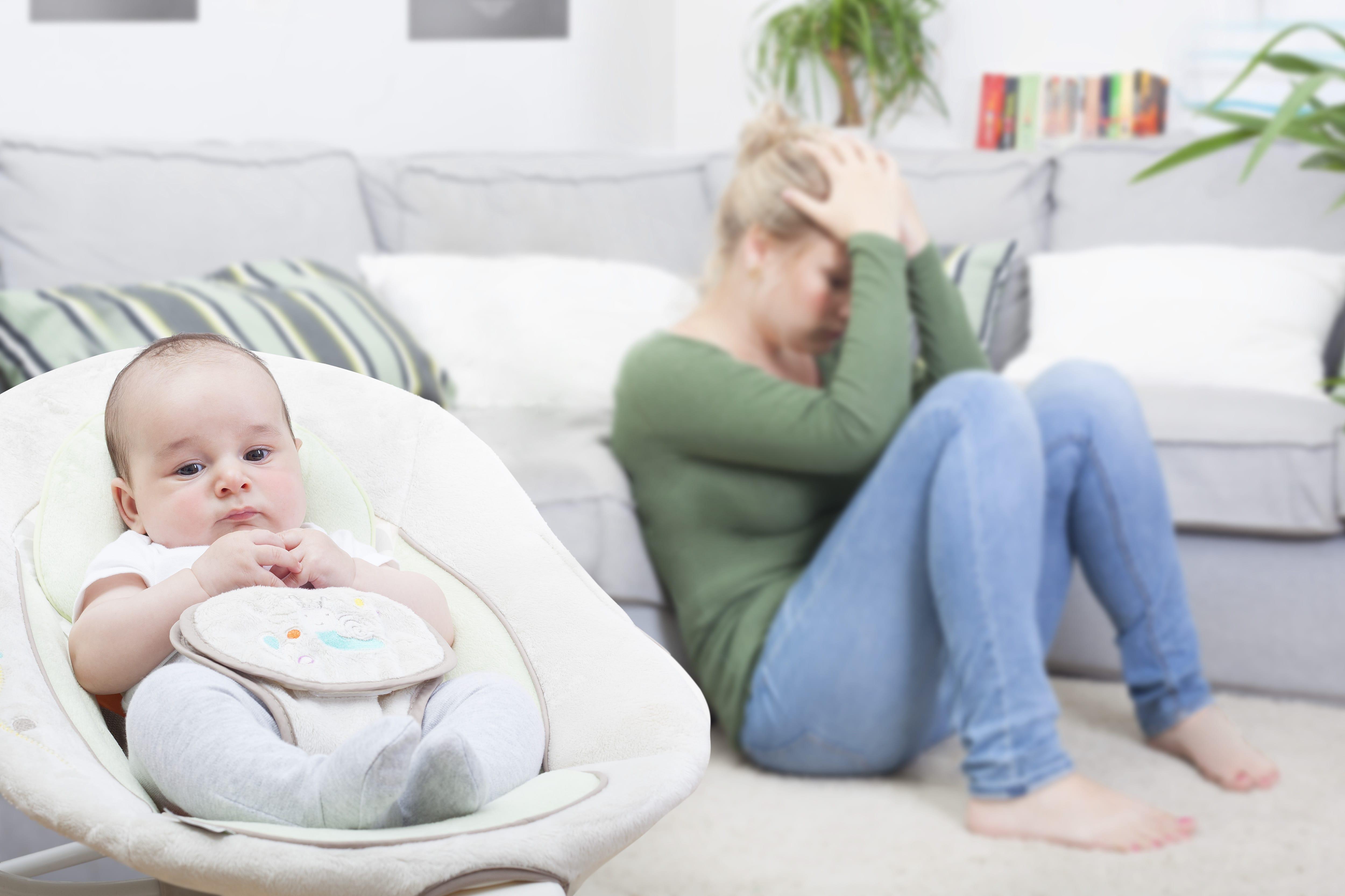 赤ちゃんの横で頭を抱える母親