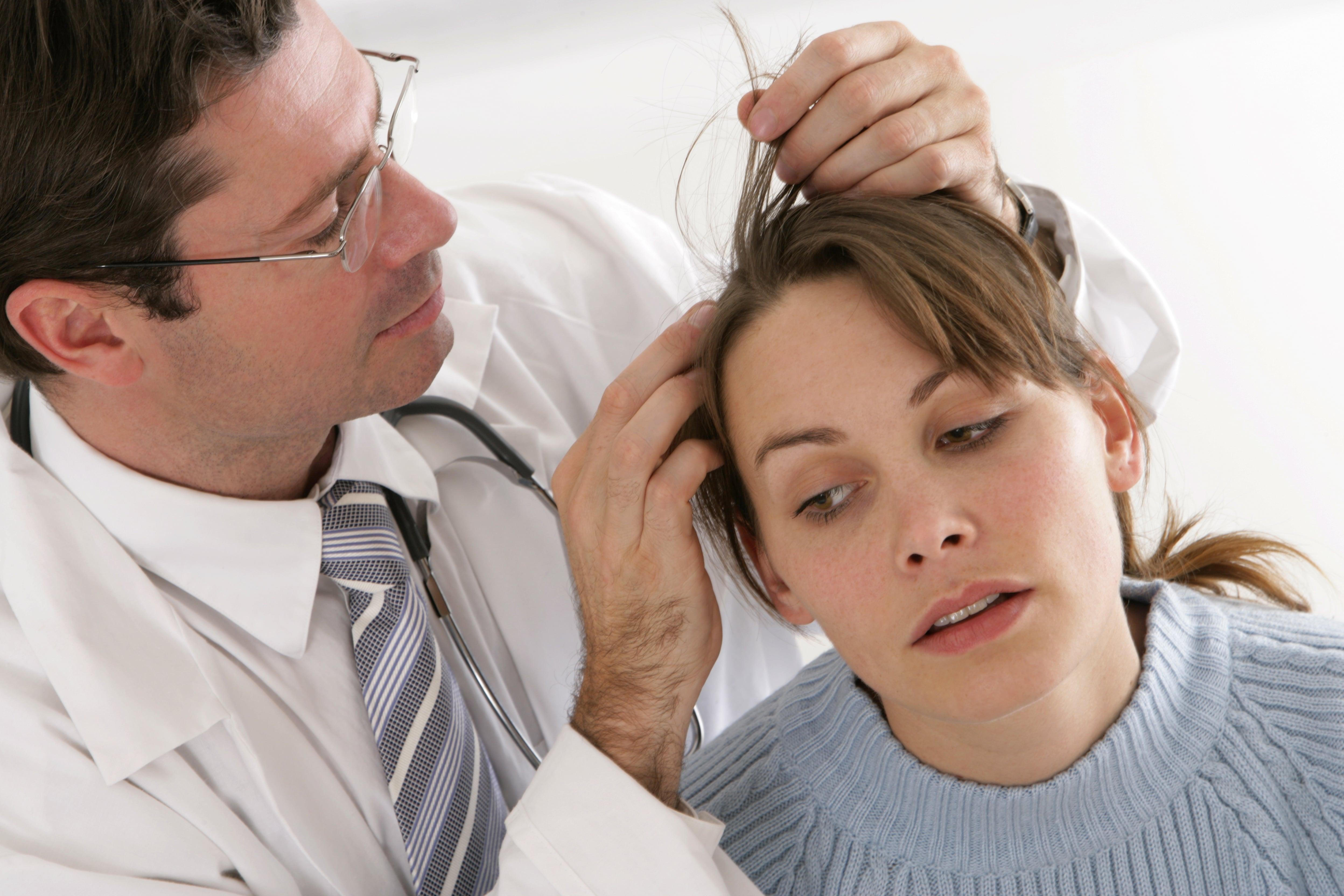 女性の頭を見る医師