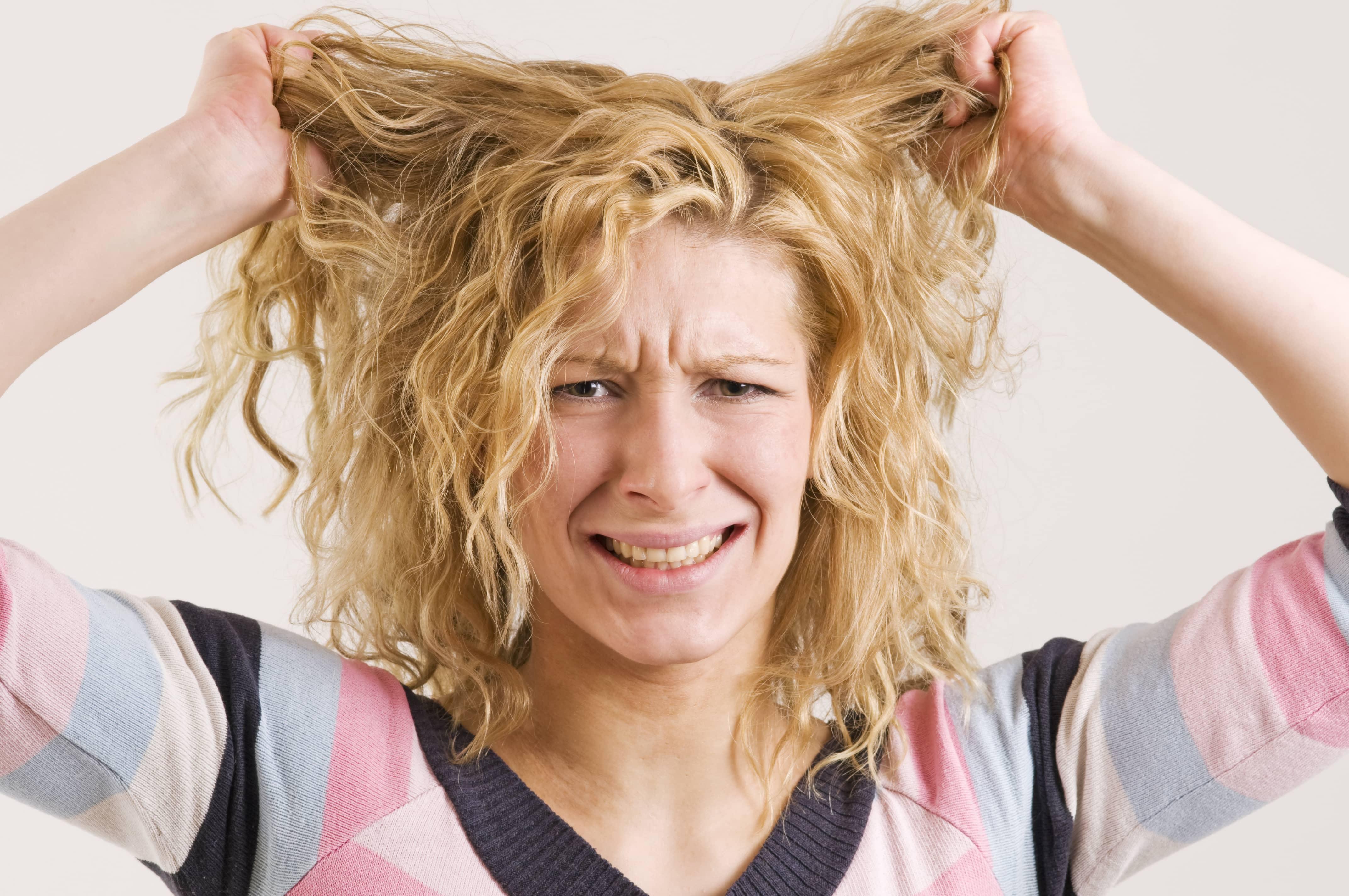 髪を持ち上げる金髪の女性