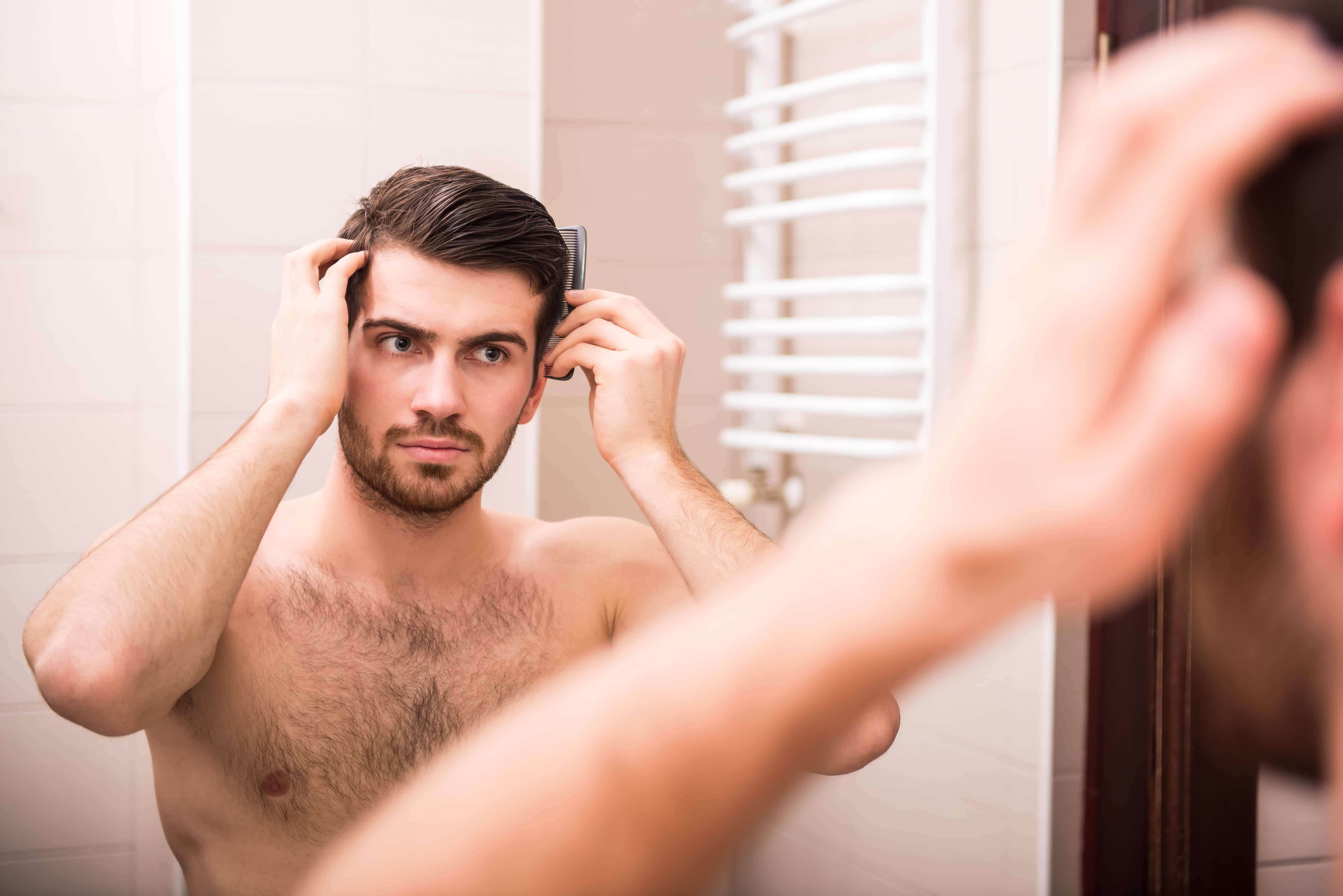 髪をセットする鏡に映った男性