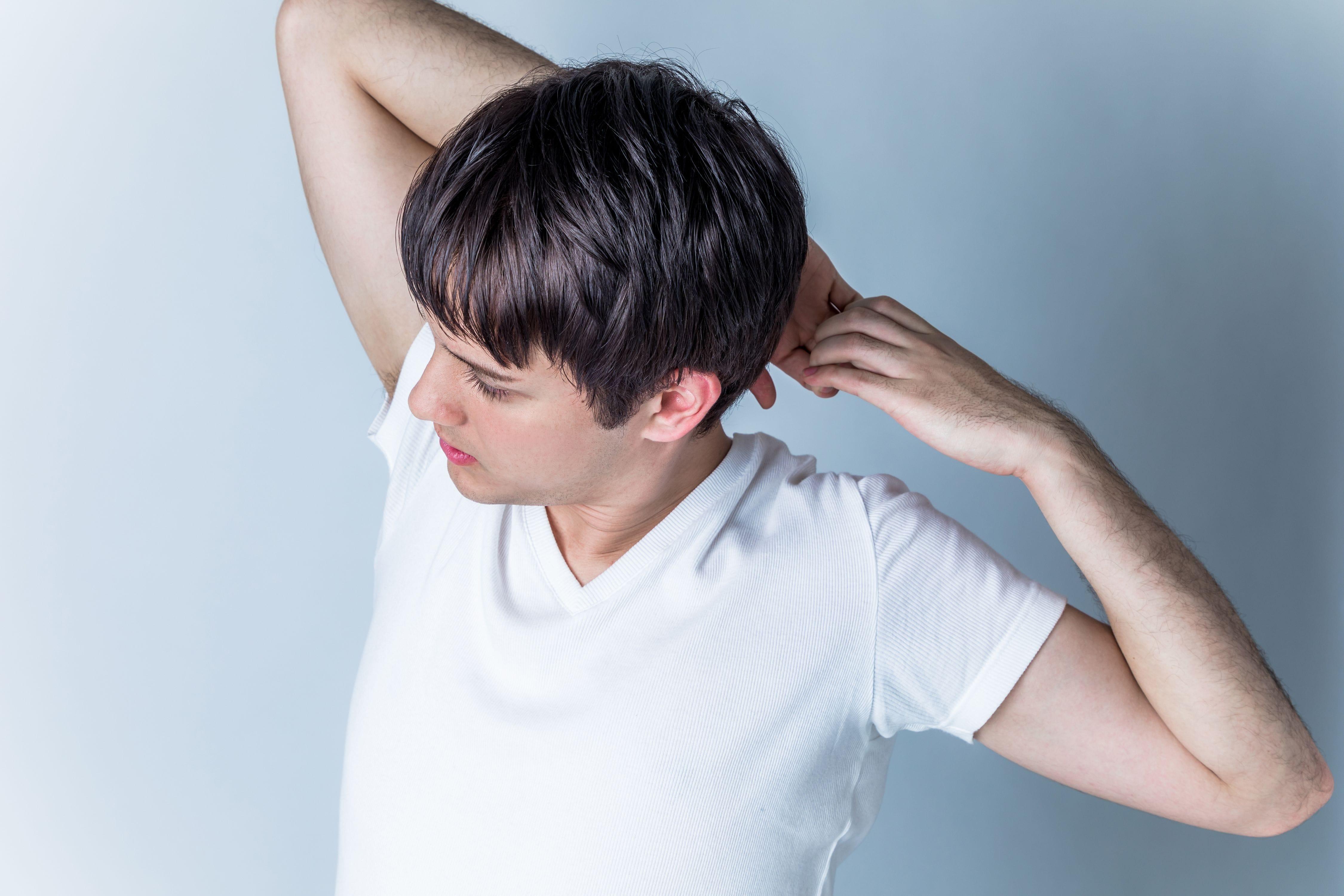 男性が頭の後ろで両指を掴みストレッチをしながら適度な運動