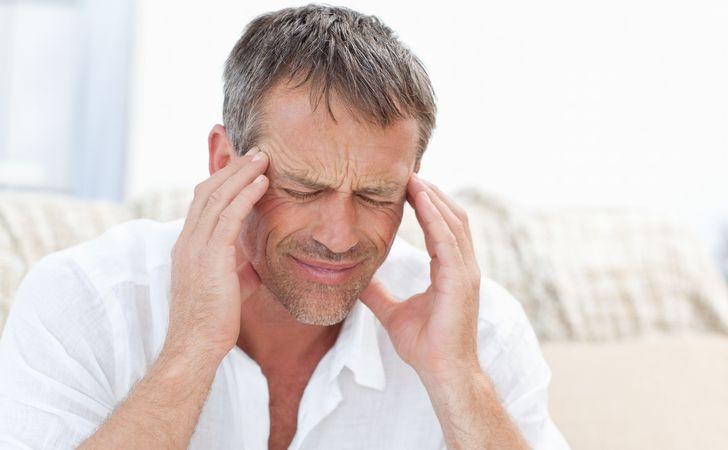 男性が頭痛で頭かかえてる
