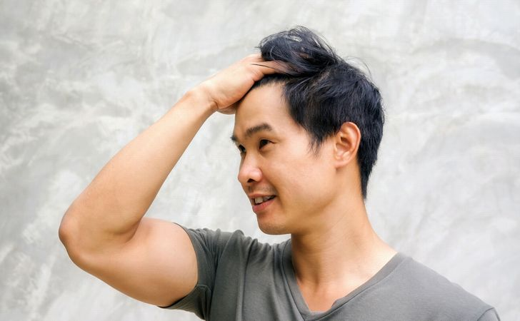 男性が髪の毛かきあげてる姿