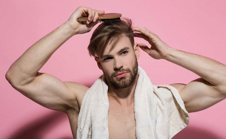 男性が髪の毛をブラシで整えてる姿