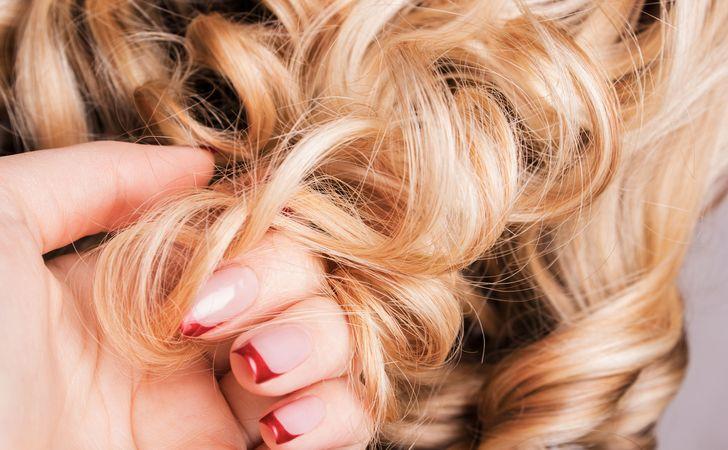 指でカールしてる髪の毛を絡ませている