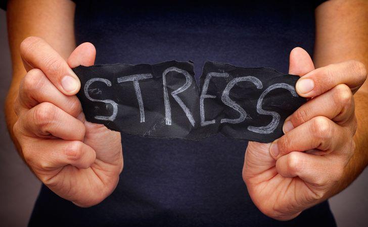 お腹の前でストレスと書いてある紙を持ってる