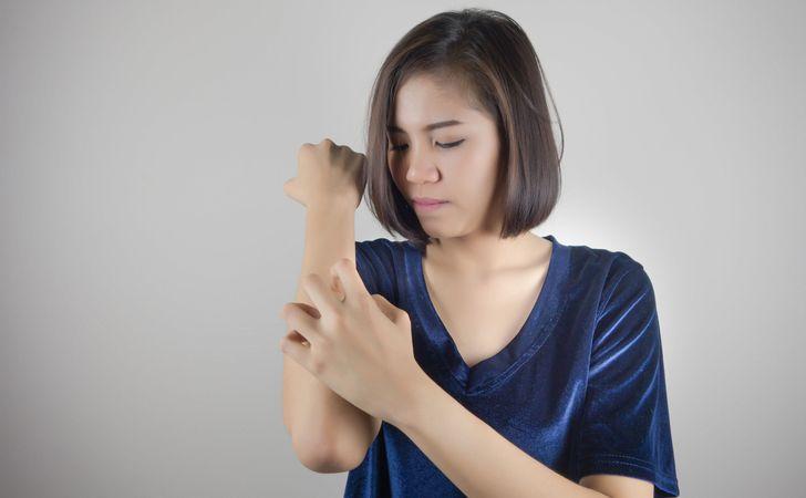 女性が左手で右腕を掻いてる姿