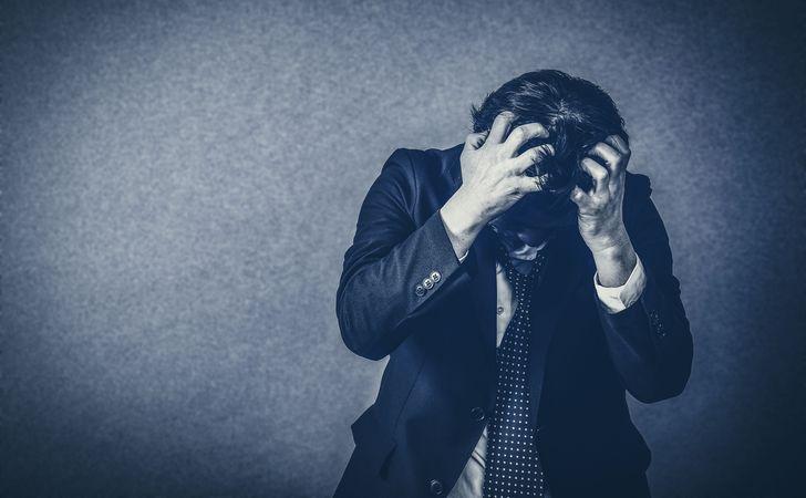 モノクロの背景の中で男性が頭を抱え悩んでる姿