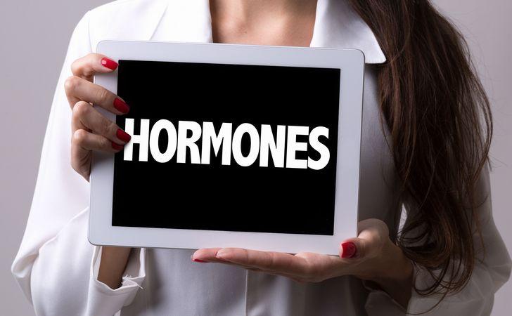 女性がホルモンと書かれたパネルを胸の前で持っている