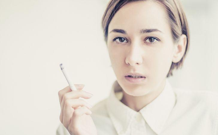 女性が火のついたタバコを右手で持っている姿