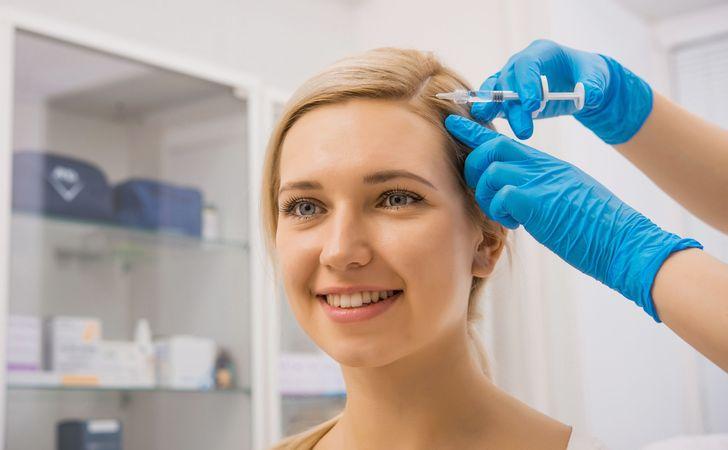 女性の頭皮の毛根に薬剤を注入しようとしている姿