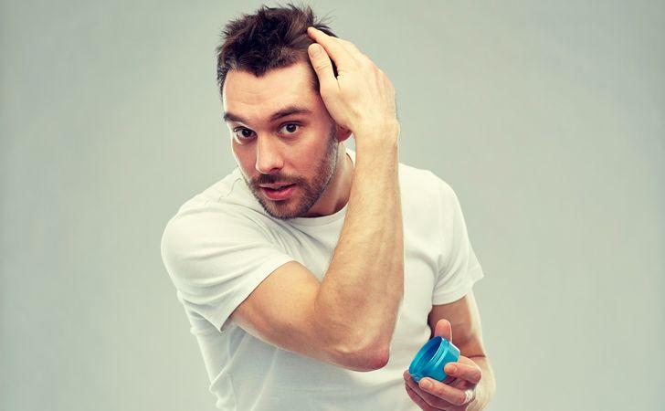 男性が整髪料持ちながら髪の毛をセットしている姿