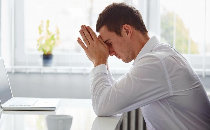 男性がパソコンの前で頭を悩ませ疲れている様子の写真