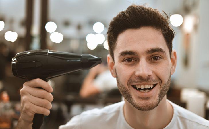 男性がドライヤーで髪を乾かしている姿